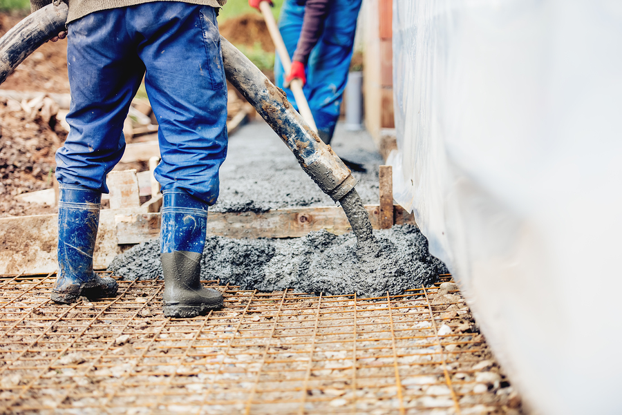 man pumping concrete for new parking lot