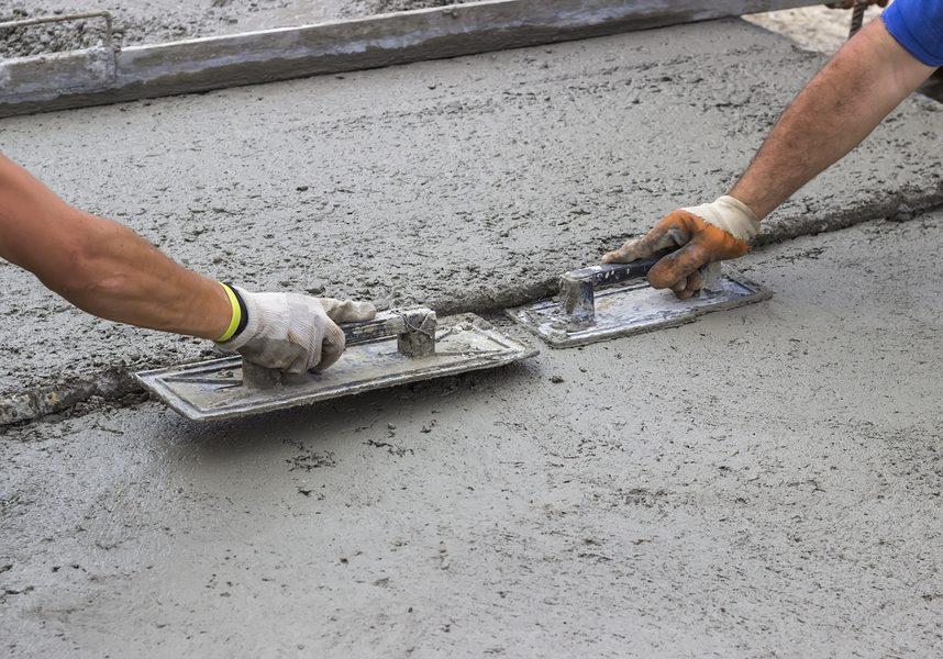 concrete workers smoothing out driveway