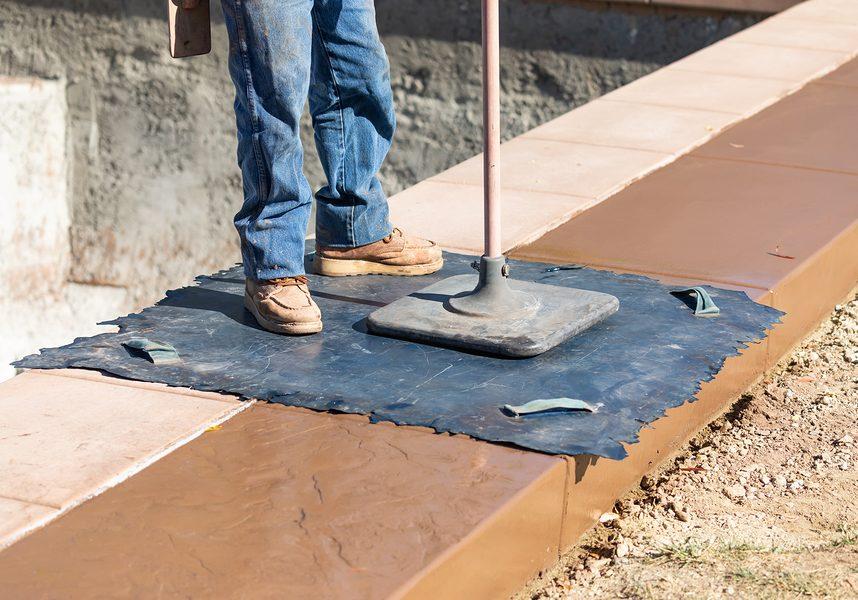 man stamping concrete on side walks